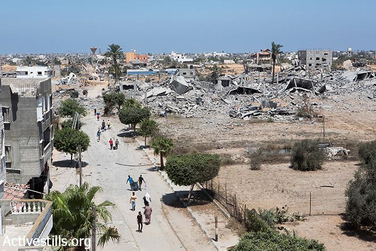 פלסטינים חוזרים לשכונת ח'וזאעה המופצצת, להוציא חפצים  וציוד אישי, ה- 3 באוגוסט 2014. (אן פאק / אקטיבסטילס)
