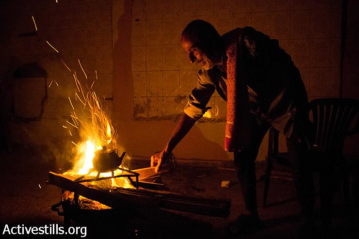 אבו עלא מכין תה על האש למשפחתו. בעקבות ההפצצות הבית נותק מחשמל ומגז. 11 באוגוסט 2014. (באסל יאזורי/אקטיבסטילס)