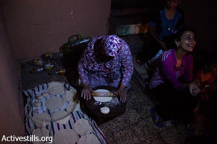 אשתו של עלווה מכינה בצק לאפיית לחם לארוחת הערב. 11 באוגוסט 2014. (באסל יאזורי/אקטיבסטילס)