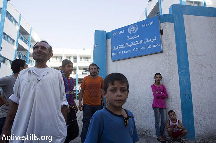 """פלסטינים עומדים מול הכניסה של """"בית הספר היסודי רמל"""" של אונר""""א המשמש מקלט זמני לפלסטינים המתגוררים בחלק הצפוני של רצועת עזה, ה- 13 ביולי 2014. (אן פאק / אקטיבסטילס)"""