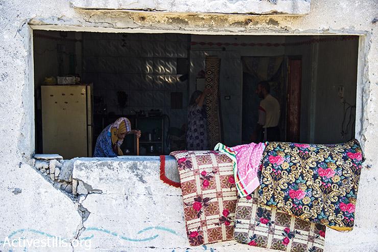 בני משפחת אבו עודה מנקים את הבית כדי שיוכלו לחיות שם בזמן הפסקת האש הזמנית. 12 באוגוסט 2014. (באסל יאזורי/אקטיבסטילס)