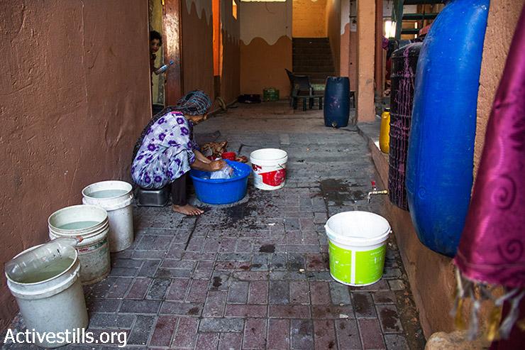 אשתו של אבו עלא, אום עלא, מכבסת בידיה בגדים, משום שאין חשמל בבית. 12 באוגוסט 2014. (באסל יאזורי/אקטיבסטילס)