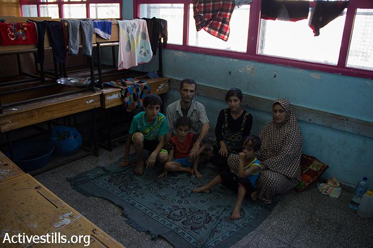 """נאהד דאוד, 41, ומשפחתו שוהים בבית הספר של אונר""""א במשך ארבעה ימים מאז שמשפחתו פונתה בעקבות אזהרות ישראליות על הכוונה לפוצץ את בית שכנם, 16 ביולי 2014. מאז שברחו, על פי נאהד, חיל האוויר הישראלי הפציץ את בית השכן שלהם, ופגע קשה בביתם. (באסל יאזורי / אקטיבסטילס)"""