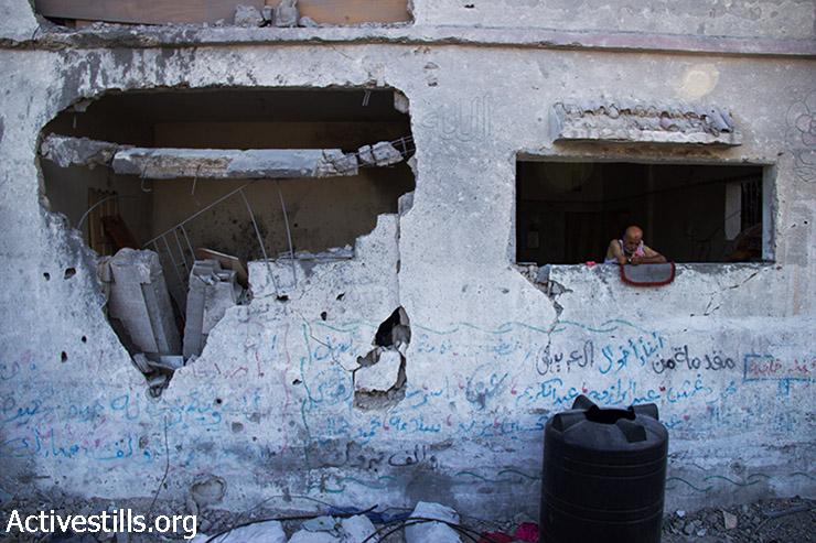 אבו עלא עומד בחלון אחד מחדרי ביתו שנהרס כליל בשעות הבוקר המוקדמות ובוחן מה נותר מן השכונה שלו. 12 באוגוסט 2014. (באסל יאזורי/אקטיבסטילס)