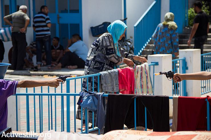 """עקורים פלסטיניים שוהים בבית הספר של אונר""""א, ביום הראשון של עיד אל פיטר, עזה, 28 ביולי, 2014. 83 בתי ספר של אונר""""א הפכו למקלטים, כמו גם בתי חולים רבים בכל רחבי הרצועה. (באסל יאזורי / אקטיבסטילס)"""