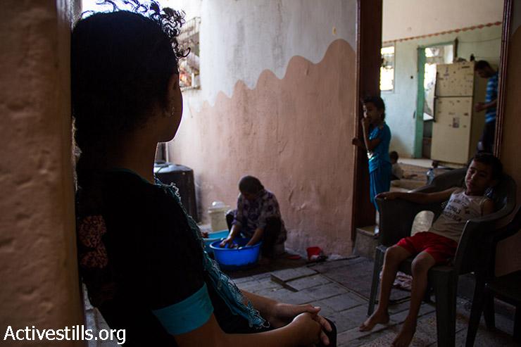 יסמין אבו עודה, בת 9, נשענת על הקיר וצופה בסבתה עושה כביסה. 12 באוגוסט 2014. (באסל יאזורי/אקטיבסטילס)