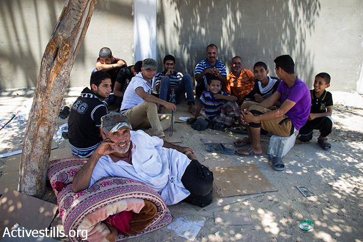 משפחה פלסטינית מעבסאן יושבת מתחת לעץ ליד בית החולים בחאן יונס. זהוא יומה העשירי של המשפחה תחת העץ, אחרי שנאלצו לברוח מביתם בשל התקיפה הישראלית. רצועת עזה, 24 ביולי 2014. (באסל יאזורי / אקטיבסטילס)