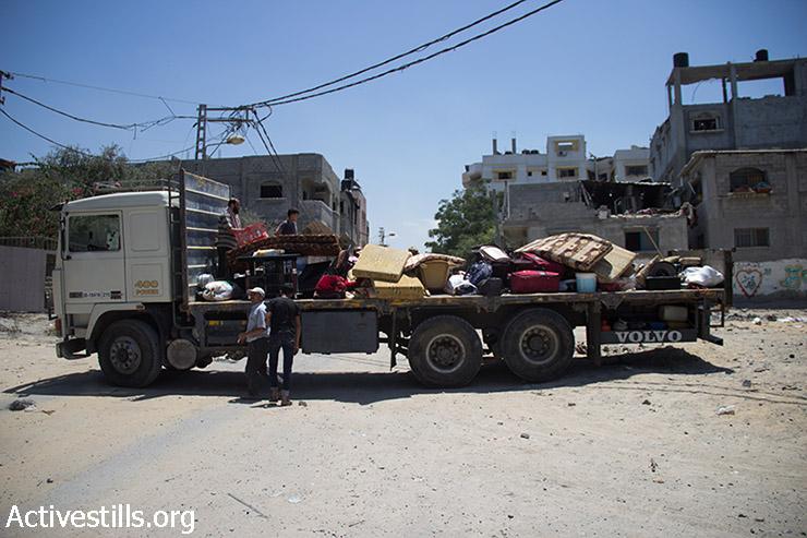 פלסטינים אוספים את חפציהם בשכונת שג'אעיה במזרח העיר עזה, במהלך הפסקת אש, 27 ביולי 2014. במהלך הפסקת האש ביום 26 ביולי, פלסטינים רבים חזרו לשג'אעיה לאמוד את הנזקים, יחד עם חובשים שניסו לחלץ פצועים או לאסוף גופות. עשרות גופות נאספו אך רבות אחרות נותרו בשטח עקב מחסור בציוד הנדרש כדי לחפור. התקיפות ישראליות הפכו את השכונה לזירת הרס מוחלט, ביניינים רבים שוטחו ואלפים נאלצו לברוח. (באסל יאזורי / אקטיבסטילס)