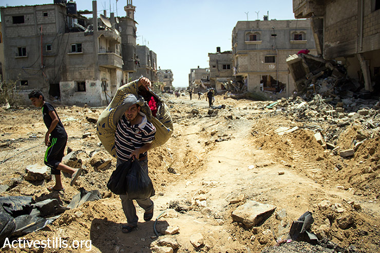 פלסטינים מנסים לחלץ חלק מרכושם אל מחוץ לכפר ח'וזאעה, מזרחית לחאן יונס, ה-1 באוגוסט 2014. מאות מהתושבים חזרו לח'וזאעה בתחילת הפסקת אש כדי לחלץ גופות וציוד. ח'וזאעה נותקה משאר רצועת עזה ונכבשה על ידי חיילים ישראליים. מספר גדול של תושבים נהרגו ונפצעו, ובתים רבים נהרסו. רוב התושבים נמלטו מההתקפות הישראליות. (באסל יאזורי / אקטיבסטילס)