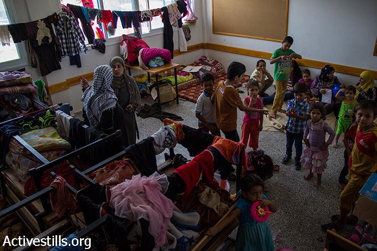 """עקורות פלסטיניות ביום הראשון של עיד אל פיטר, שוהות בכיתה של בית הספר של אונר""""א שהפך למקלט, ה-28 ביולי 2014. (באסל יאזורי / אקטיבסטילס)"""
