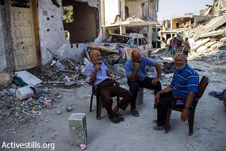 אבו עלא יושב עם שכניו ומחליפים בדיחות על צבא הכיבוש. 12 באוגוסט 2014. (באסל יאזורי/אקטיבסטילס)