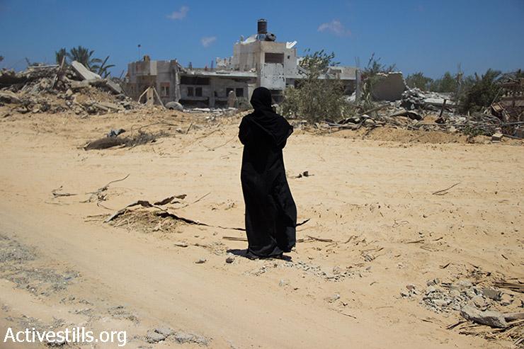 """אישה פלסטינית מביטה לעבר שכונת ח'וזאעה שהופגזה על ידי כוחות ישראליים, ברצועת עזה, 3 באוגוסט, 2014. ח'וזאעה ספגה הפגזה כבדה ביום שני בלילה, ה-21 ביולי. הצבא הישראלי הורה לכל תושבי הכפר, כמעט 10,000 בני אדם, לעזוב. ח'וזאעה נותרה שטח צבאי סגור, ורק המשלחת הבינ""""ל של הצלב האדום מורשית להגיע לזמנים קצרים אל הכפר לפינוי חלק מהפצועים וההרוגים. רוב התושבים נמלטו מהכפר אך חלק נשארו מאחור. (באסל יאזורי / אקטיבסטילס)"""
