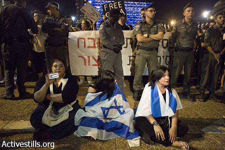 שתי מפגינות ימין ומפגינת שמאל בכיכר רבין (קרן מנור / אקטיבסטילס)