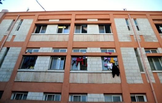 כביסה מתנפנפת תלוי על חלונות בית החולים שנראה כמו מחנה פליטים או אכסניה. (צילום: יעל מרום)