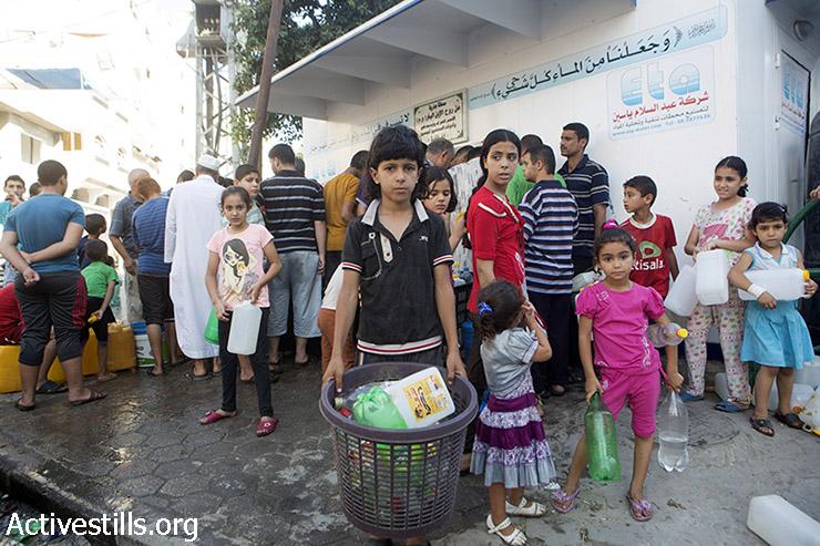 פלסטינים אוספים מים במחנה הפליטים שאטי בעזה, ה-2 באוגוסט, 2014. לפי דיווחי אוצ'ה, ל- 1.5 מיליון אנשים בעזה שאינם במקלטים יש גישה מאוד מוגבלת למים, אם בכלל. (באסל יאזורי / אקטיבסטילס)