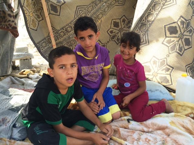 שלושה ילדים מבית חנון יושבים תחת עץ מול הריסות ביתם (סאמר בדאווי)