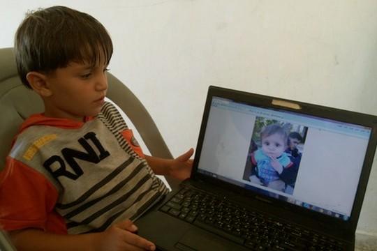 מחמד עם תמונת אחיו, מוסא, שנהרג בתקיפה יחד עם שני הוריהם ואחותו. (עאוני פרחאת)