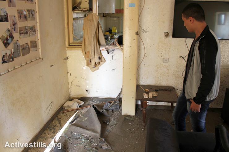 צעיר פלסטיני בוחן את הנזק שנגרם למועדון הספורט לבני נוער בעקבות פשיטת הצבא לשכם, 3 בספומבר, 2014. הצבא עצר את חוסאם אל-דין אבו ריאלה, 26, שנפצע מירי אש חיה ברגלו, ואילו חמישה נוספים הצליחו להמלט. (אחמד אל-באז/אקטיבסטילס)