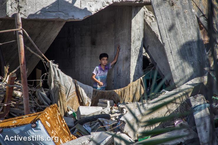 ילד פלסטיני עומד על חורבות ביתו בשכונת שג׳יעה, מזרח העיר עזה, ה-4 לספטמבר, 2014. (אקטיבסטילס)