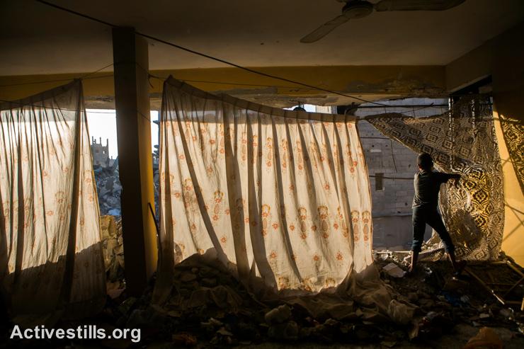 ילד פלסטיני מסתכל על ההריסות,  שכונת שג׳יעה, מזרח עזה, ה-4 לספטמבר 2014. (אקטיבסטילס)