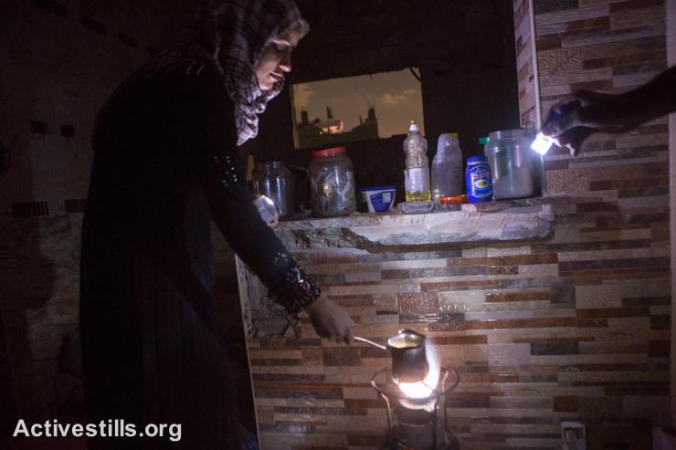 בני משפחת עאטש מחממים מים בחדר שנשאר על תילו בביתם ההרוס, שג׳יעה, ה-5 לספטמבר 2014. (אקטיבסטילס)