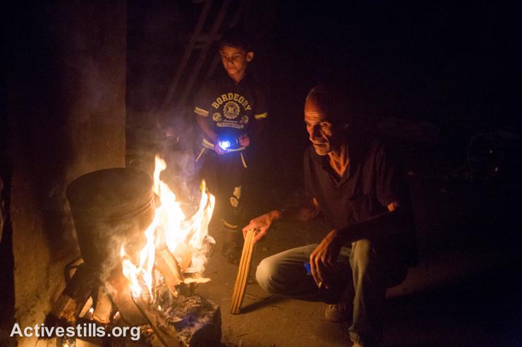 בני משפחת עאטש מדליקים אשר בחדר שנשאר על תילו בביתם ההרוס, שכונת שג׳יעה, ה-5 לספטמבר 2014. (אקטיבסטילס)