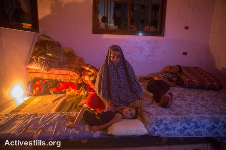 בני משפחת עאטש יושבים בחדר המואר בנרות שנשאר על תילו בביתם ההרוס, שג׳יעה, ה-5 לספטמבר 2014. (אקטיבסטילס)