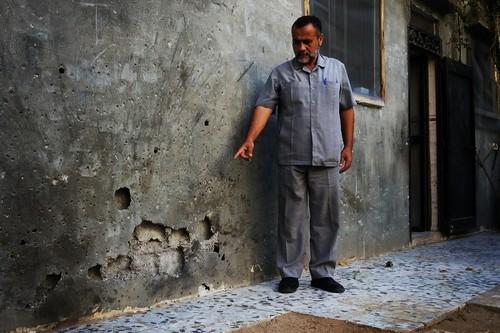 עיסאם מצביע על מקום פגיעת הטיל בחצר הבית צילום: עאוני פרחאת