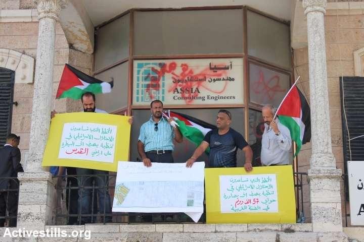 פעילים מניפים שלטים ממרפסת בניין החברה ברמאללה. (אחמד אל-באז/אקטיבסטילס)