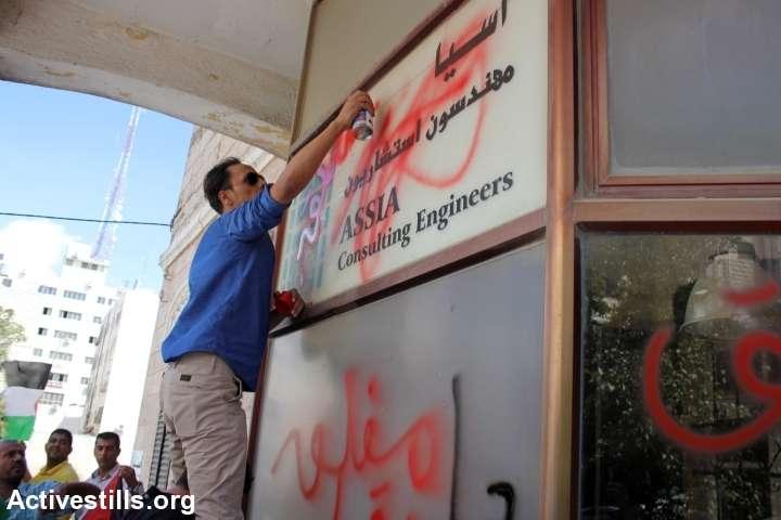 פעיל מרסס גרפיטי בכניסה לבניין החברה ברמאללה. (אחמד אל-באז/אקטיבסטילס)