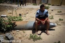 חאסן שאמדי יושב על טיל ישראלי שלא התפוצץ לאחר תקיפה ישראלית שהרסה את ביתו יום קודם לכן, בשכונה תל אל-האווה בעיר עזה, ה-14 ליולי, 2014. (אן פאק/אקטיבסטילס)