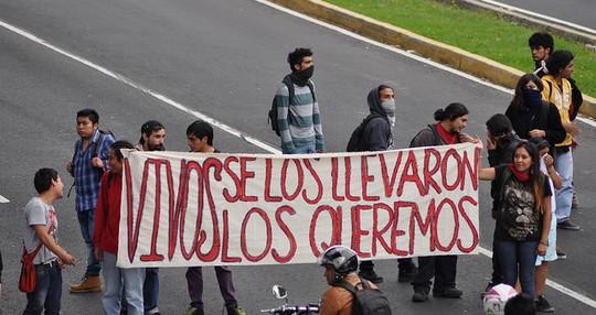 """הפגנה במקסיקו לאחר היעלמות 43 הסטודנטים. בשלט כתוב """"חיים לקחתם אותם, חיים אנחנו רוצים אותם"""". (Rodrigo Barquera, םליקר CC BY-NC-SA 2.0)"""