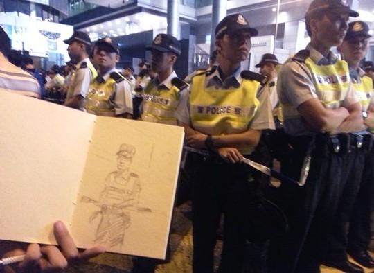 אחד המפגינים מצייר דיוקן של שוטר (צילום: אמנון לוטן)