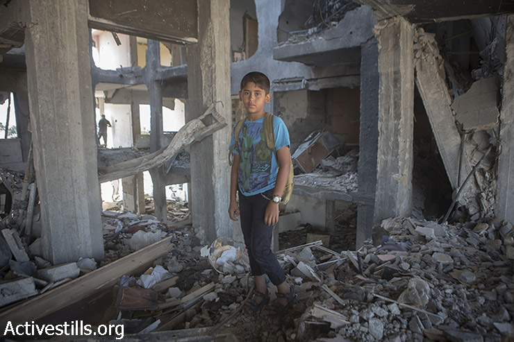 מוחמד, בן 11, עומד בין שרידי ביתו במגדלי אל נדא בבית חאנון שבצפון רצועת עזה לאחר שנהרסו על ידי הפצצות ישראליות. 21 בספטמבר, 2014. במגדלים היו 90 דירות, בהם התגוררו משפחות רבות.(אקטיבסטילס)