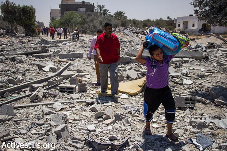 לד פלסטיני נושא חפצים אישיים שחולצו מהכפר ח'וזאעה, שעבר התקפות אינטנסיביות ונהרס במידה רבה במהלך המתקפה הישראלית. 1 באוגוסט, 2014.(אקטיבסטילס)