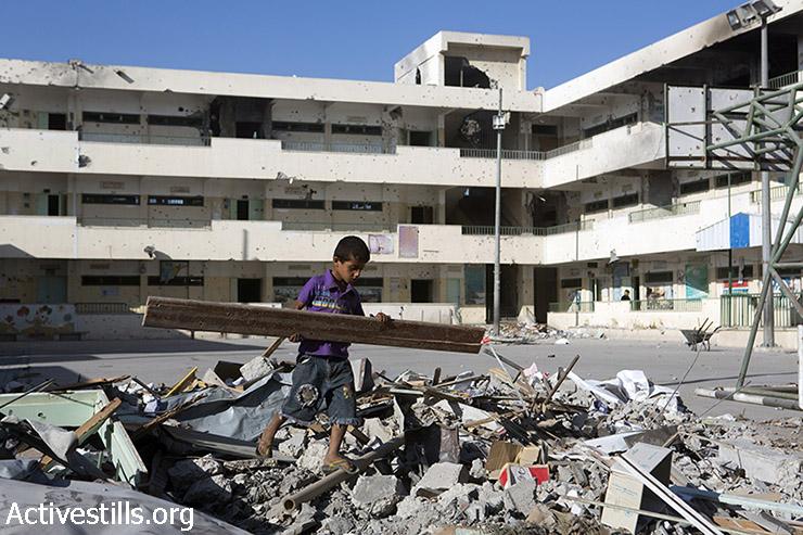 ילד מוציא חתיכות עץ מבין ההריסות שנאספו בבית הספר הממשלתי סובחי אבו קרש. בית הספר, הממוקם בשכונת שג'עיה במזרח עזה, נפגע על ידי ההפצצות, 4 בספטמבר, 2014. (אקטיבסטילס)
