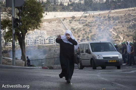 אשה בורחת מרימון הלם בכניסה לשכונת וואדי ג׳וז (אקטיבסטילס)
