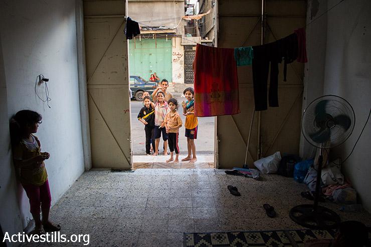 משפחת אל-זענין אשר ברחו מביתם בבית חאנון חיים בחנות ריקה ללא חלונות או שירותים סמוך לבית החולים כמאל עדוואן בג'באליה. 24 ביולי, 2014. (אקטיבסטילס)