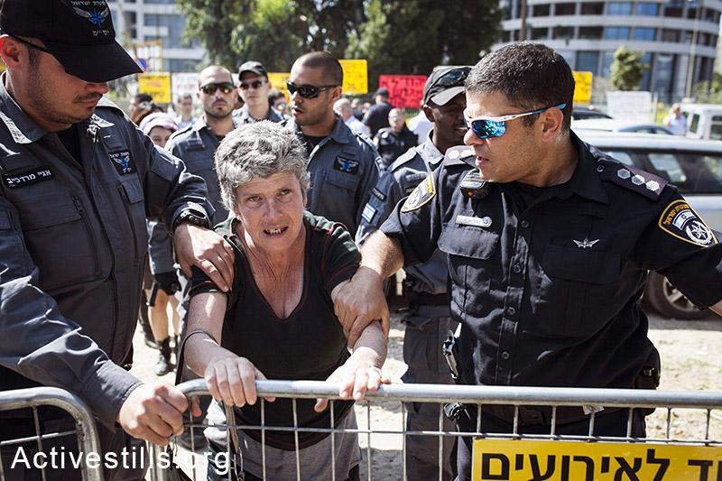 שוטרי מג״ב הודפים את פעילת הדיור הציבורי זהבה גרינפלד במהלך פינוי של שש משפחות בשכונת גבעת עמל, תל אביב, 27 מרץ, 2013. שירז גרינבאום/אקטיבסטילס