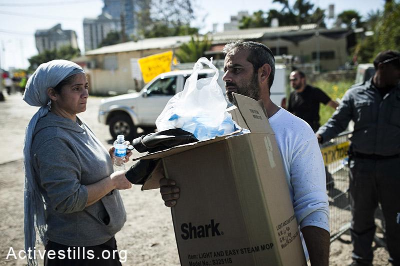 משפחת לוי מפנה חפצים בזמן שביתם נהרס על ידי עובדי קבלן, במהלך פינוי של שש משפחות, בגבעת עמל, תל אביב, 27 מרץ, 2013. שירז גרינבאום/אקטיבסטילס