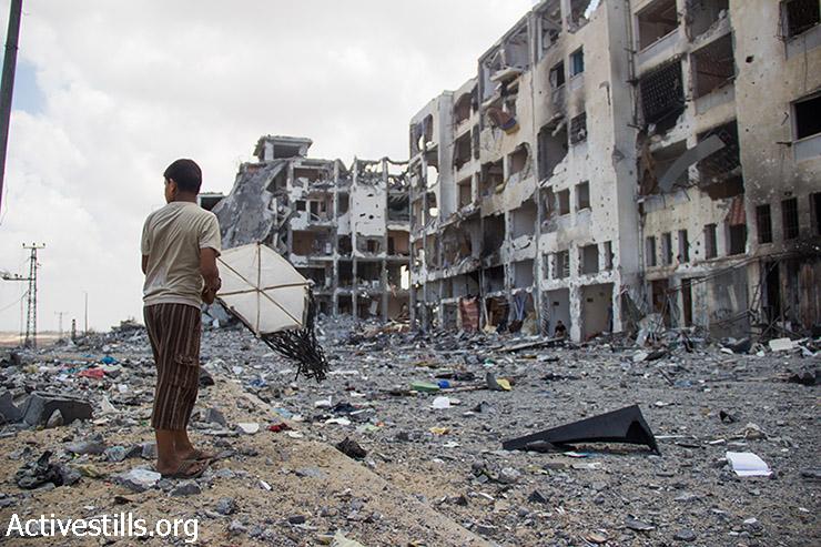 ילד פלסטיני עם עפיפון עומד מול הריסות מגדלי אל נדא בבית חנון, צפון רצועת עזה. במגדלים היו 90 דירות. (אקטיבסטילס)