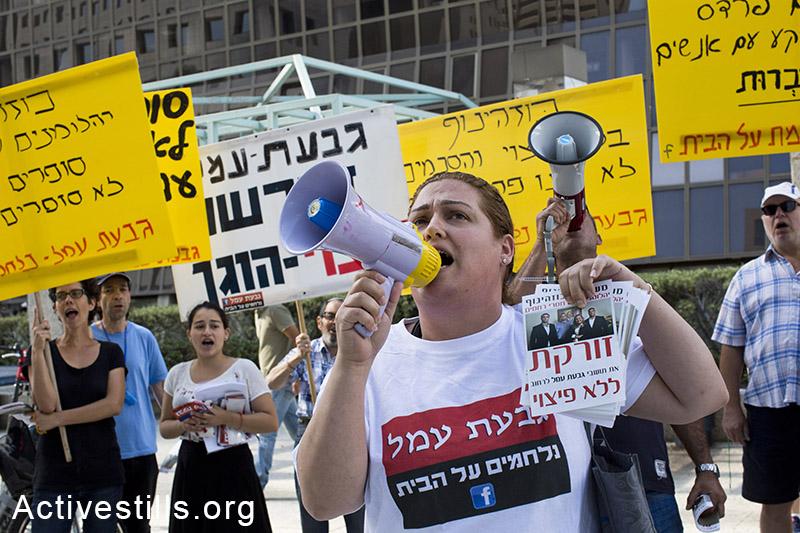 תושבי גבעת עמל ופעילים תומכים מפגינים בכניסה למשרדי משפחת כוזהינוף ברמת גן במחאה נגד פינוי משפחות בשכונה, 1 מאי, 2014. קרן מנור/אקטיבסטילס