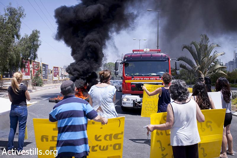תושבי גבעת עמל חוסמים כביש בכניסה לשכונה במחאה נגד פינוי משפחות. שלושה מתושבי השכונה נעצרו במהלך הפעולה.  27 יוני, 2014. שירז גרינבאום/אקטיבסטילס