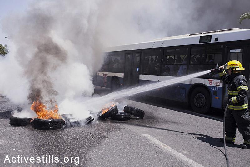 כבאי מכבה צמיג במהלך חסימת כביש בכניסה לשכונה במחאה נגד פינוי משפחות. שלושה מתושבי השכונה נעצרו במהלך הפעולה. 27 יוני, 2014. שירז גרינבאום/אקטיבסטילס