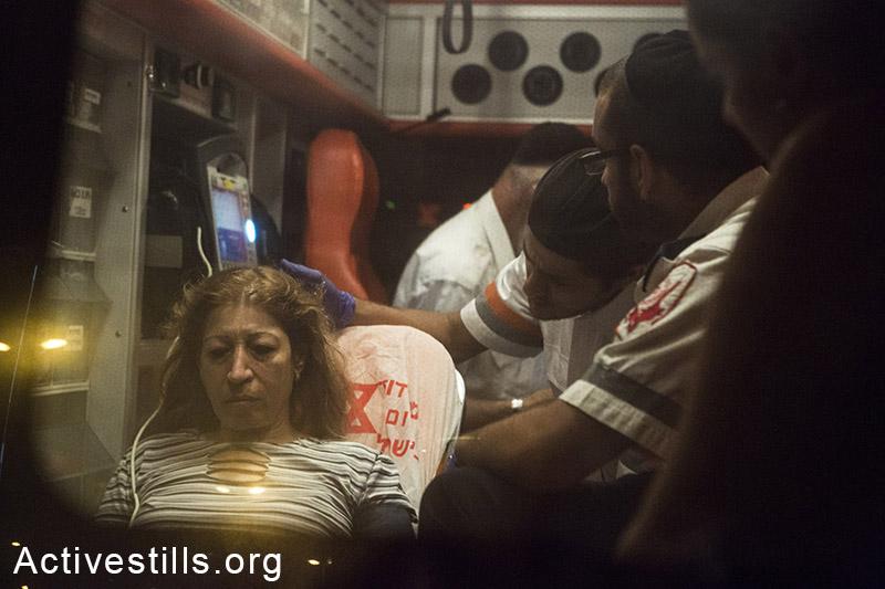אסנת חמיאס, תושבת גבעת עמל, מטופלת על ידי חובשים לאחר שהתמוטטה במהלך מחאה נגד פינוי צפוי של משפחות בשכונה, גבעת עמל, 15 ספטמבר, 2014. קרן מנור/אקטיבסטילס