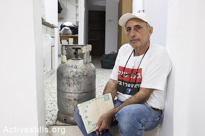 מנשה חליף יושב ליד בלון גז במהלך פינוי משפחות בגבעת עמל. מנשה נעצר על ידי כוחות מג״ב וביתו נהרס. תל אביב, 17 ספטמבר, 2014. קרן מנור/אקטיבסטילס
