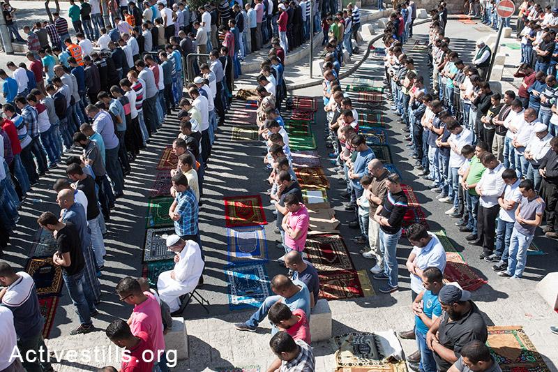 פלסטינים מתפללים מחוץ למסגד אל אקסה באזור ראס אל-עמוד בשל הגבלות הכניסה למתחם, מזרח ירושלים, 24 אוקטובר, 2014. (אקטיבסטילס)