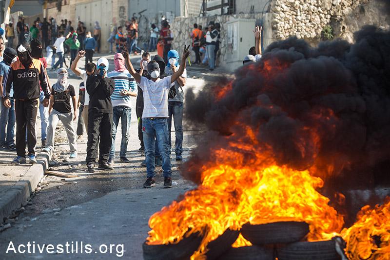 מה שמבעיר את ירושלים איננו מצב כיתות הלימוד. צעירים פלסטינים מבעירים צמיגים בשכונת עיסוואיה לאחר תפילת יום השישי, מזרח ירושלים, 24 אוקטובר, 2014. (אקטיבסטילס)