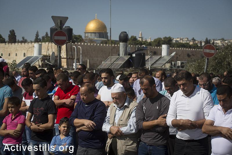 פלסטינים מתפללים מחוץ לאל אקסה באזור ראס אל-עמוד בשל הגבלות הכניסה למתחם, מזרח ירושלים, 24 אוקטובר, 2014. (אקטיבסטילס)
