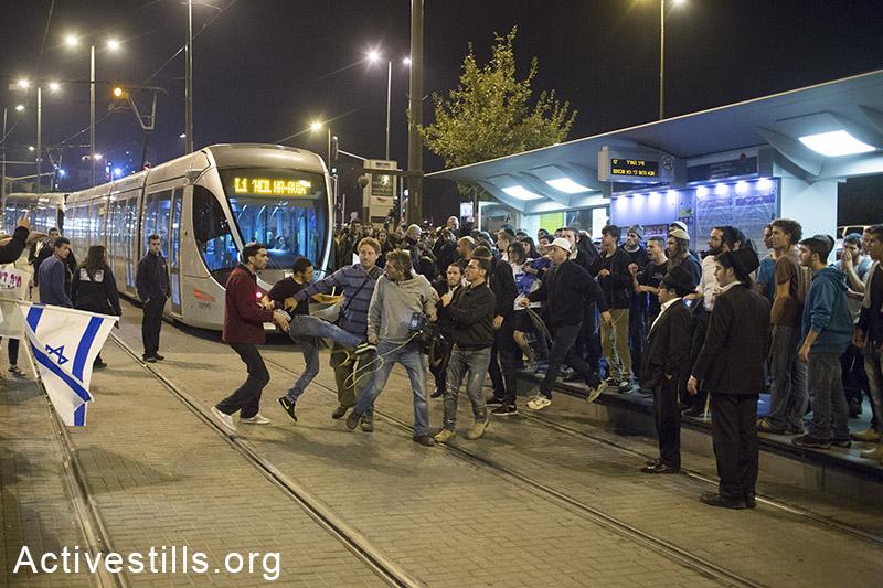 מפגיני ימין מרביצים לעיתונאי במהלך הפגנה תחת הכותרת ׳נקמה׳, באזור תחנת הרכבת הקלה בה התרחש אירוע הדריסה, מזרח ירושלים, 23 אוקטובר, 2014. (אקטיבסטילס)